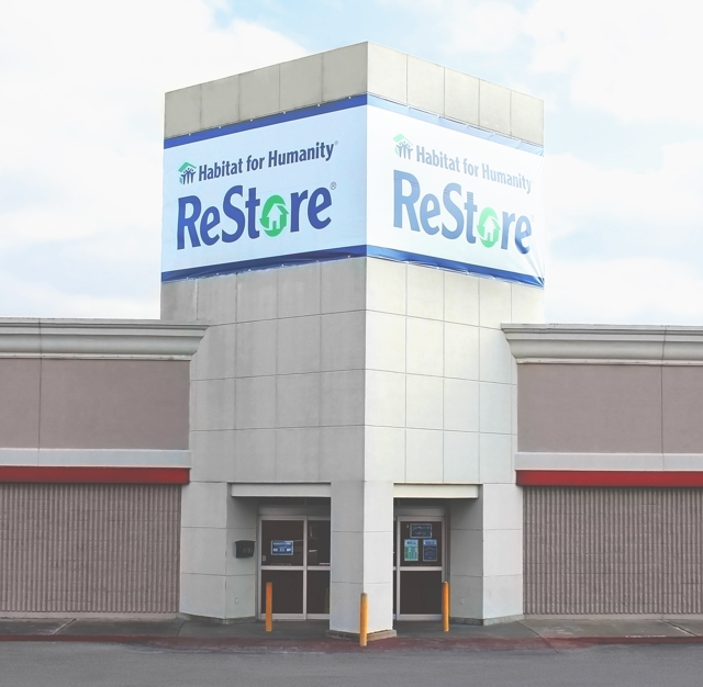A photo of the Webster ReStore with a banner across the building, reading