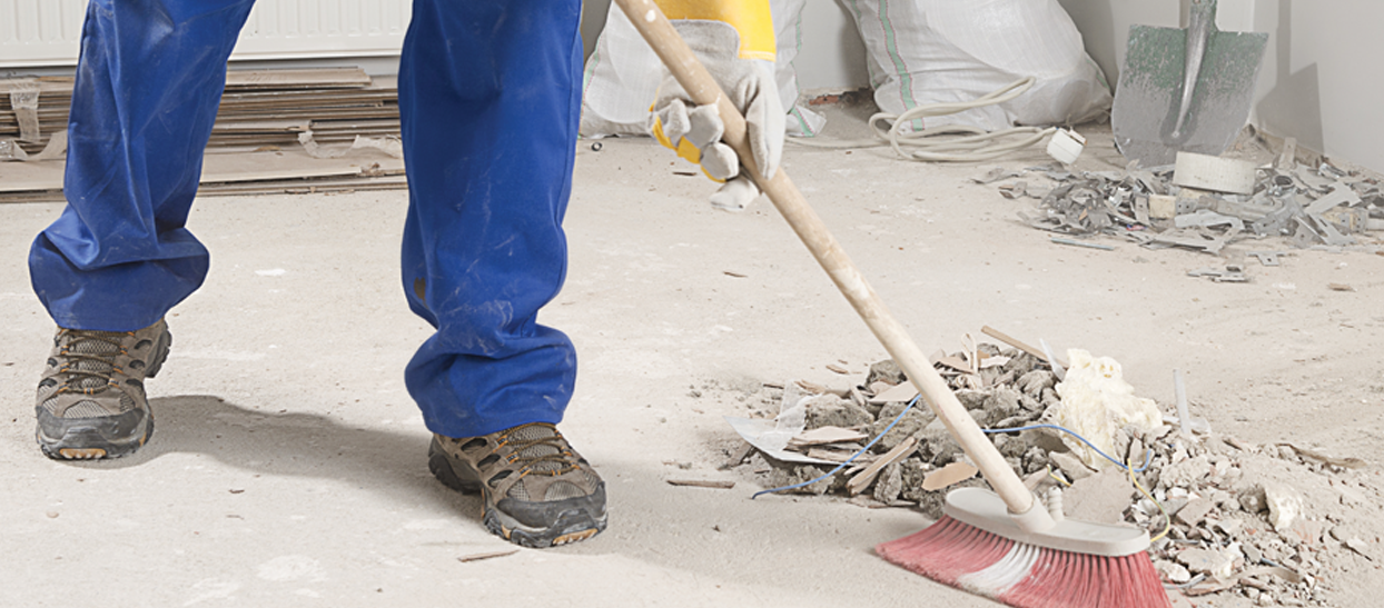 A photo of someone sweeping up construction debris.