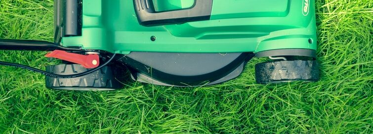 A photo of a lawn mower on grass.